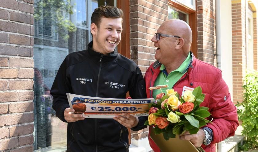 Samuel uit Nijmegen wordt door Postcode Loterij-ambassadeur Gaston verrast met de PostcodeStraatprijs-cheque ter waarde van 25.000 euro.