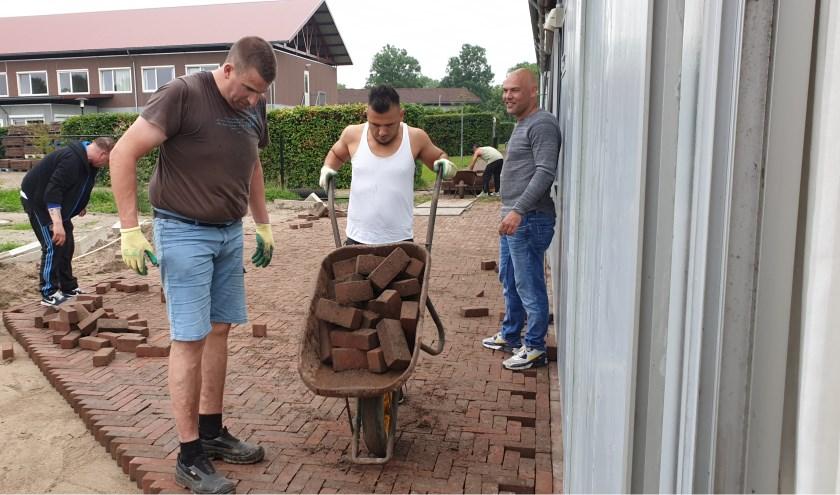 Met hulp van een medewerker van AllGroen is het terras achter het ProefLokaal aangelegd. (foto: Buitenzinnig)