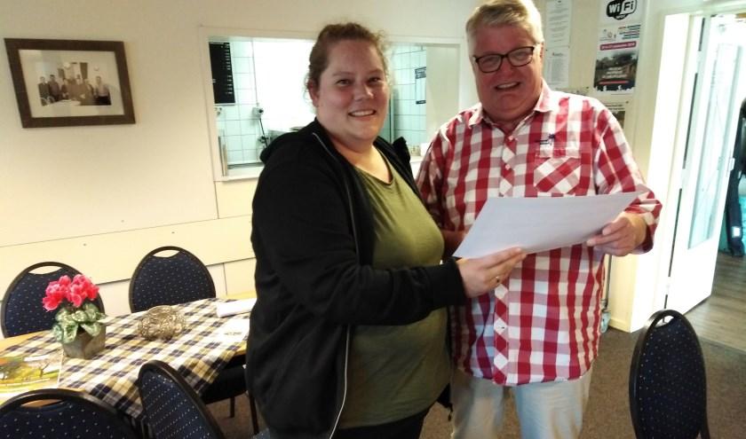 Judith Steenkamp van JuNiMo is blij met de cheque die ze krijgt uit handen van Hennie Horst van Wandelkring DIO.