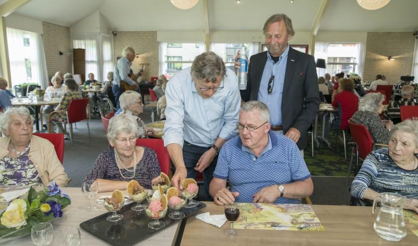 Leden van Rotary Brummen-Engelenburg serveren ijs met slagroom aan de bewoners van Tolzicht.