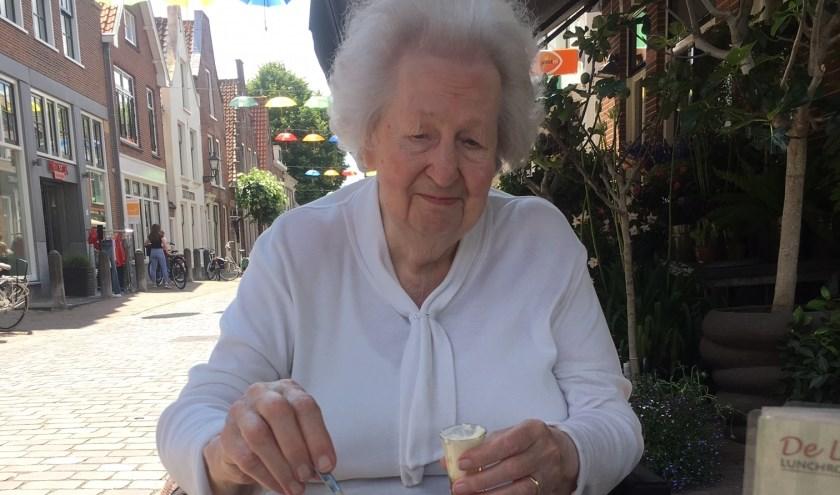 Mevrouw Van Breukelen geniet van het mooie weer, de fleurige binnenstad  én koffie met gebak. (Foto: vrijwilligster Nel van Rooijen) .