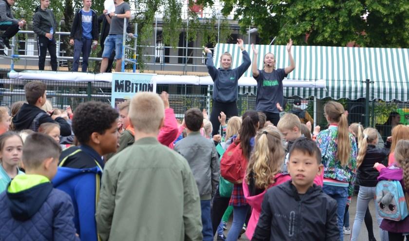 De kinderen werden door trainsters van MBition geïnspireerd op te warmen.. Achter hen overlegt jongerenwerker Eno met de initiatiefnemers.