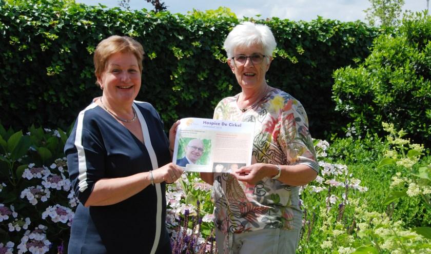 Vrijwilliger Wil Buitenhuis (rechts) krijgt de nieuwe jaarkrant van hospice De Cirkel overhandigd van bestuurslid Heleen Roos.