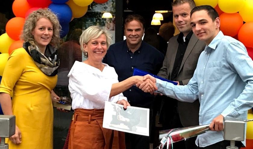 Damian Stijker ontvangt niet alleen een diploma, maar ook een arbeidscontract én een feliciatie van wethouder Niels van den Berg.