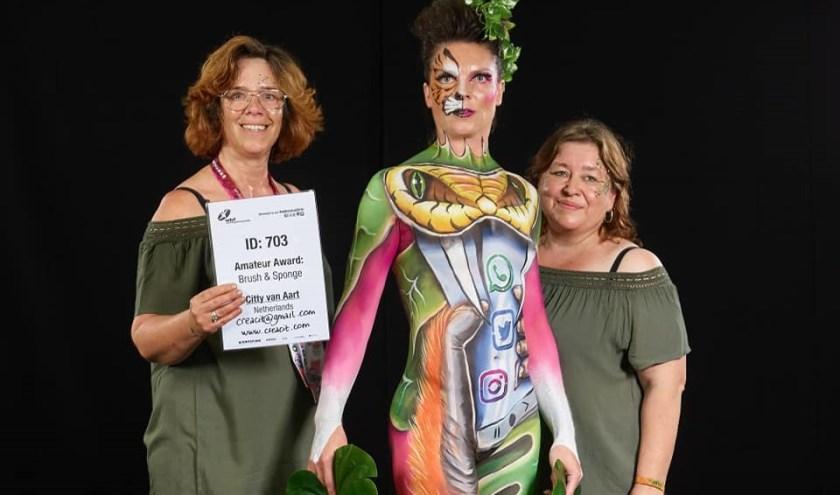 V.l.n.r: Bodypaintster Citty van Aart, model Mariella Wagenaar en assistente Karin Minderhoud op het WK Body and Sponge. Foto: WB Production