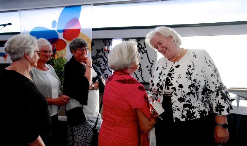 Marianne van Eechoud (rode jurk) bedankt burgemeester Marianne Schuurmans voor haar betrokkenheid en aandacht. (foto: Kirsten den Boef)