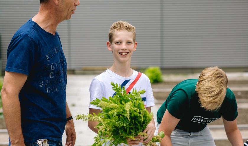 Leerlingen brugklas oogsten uit nieuwe schooltuin. (Foto: Arjan van der Plaat)