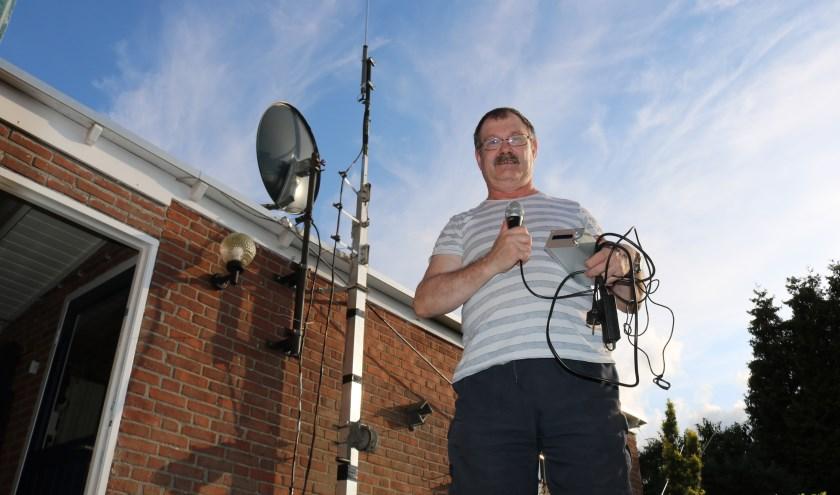 Gerrit ten Pas met zijn zendinstallatie in de handen en links de in elkaar geschoven zendmast. (Foto: Arjen Dieperink)