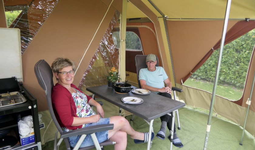 """Het echtpaar Peter en Anita Pelzer onder de luifel voor hun vouwwagen op boerderijcamping De Linde. """"Het is een schone camping met hele vriendelijke mensen"""", aldus Anita."""
