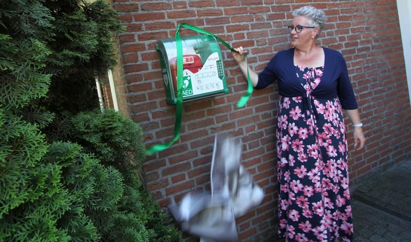 """Wethouder Mariënne van Dongen onthult de AED door het weghalen van een doek. """"Supermooi dat je dit als buurt in de wijk kunt regelen."""" FOTO: Ad Adriaans."""