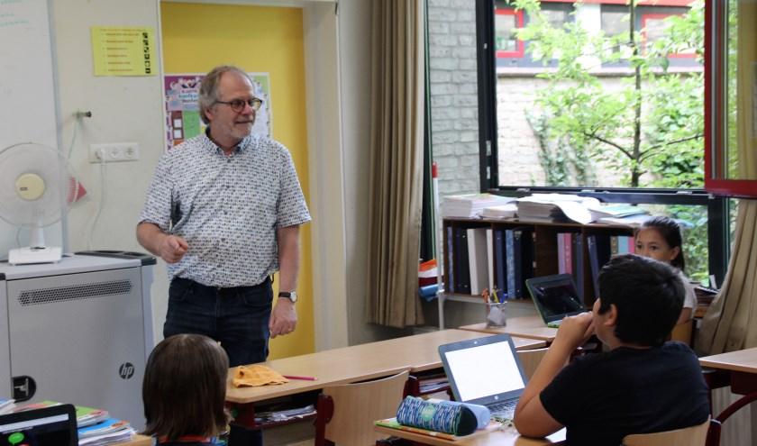 Luc Drenth legt nog even wat uit aan de kinderen van de Da Costaschool. Hij gaat genieten van een welverdiend pensioen. (Foto: Dick Baas)