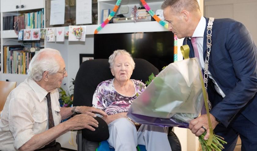 Locoburgemeester John van den Hoven overhandigt de bloemen aan het diamanten bruidspaar. Foto: Johan Wouters/Pix4Profs
