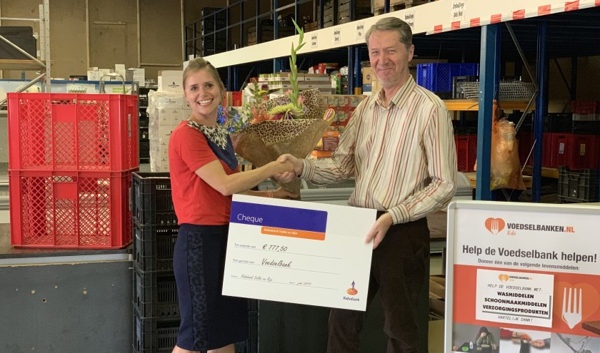 Marieke Kuijsten, manager Marktteam Ede-Bennekom van Rabobank Vallei en Rijn biedt de cheque aan, aan voorzitter Just Hageman van de Voedselbank.