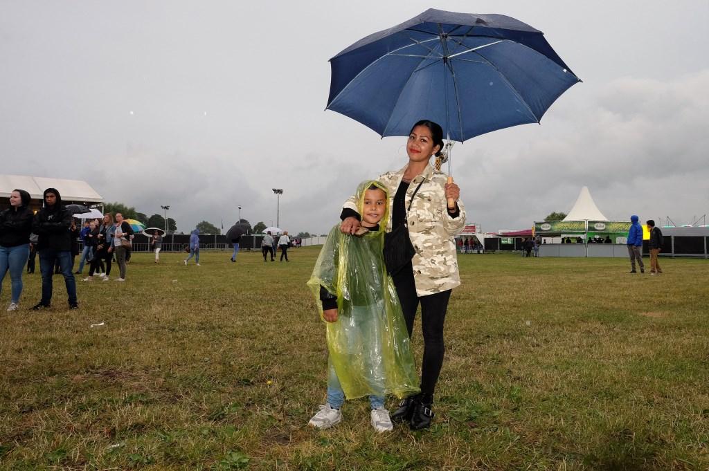 moeder en zoon uit opheusden trotseren de regen. (Foto: Max Timons)   © DPG Media