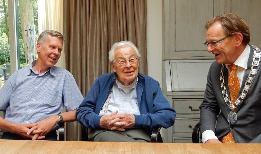 De bijna-jarige heer Wieriks wordt gefeliciteerd door burgemeester Koos Janssen. Zoon Anthony kijkt lachend toe. Foto: Asta Diepen Stöpler