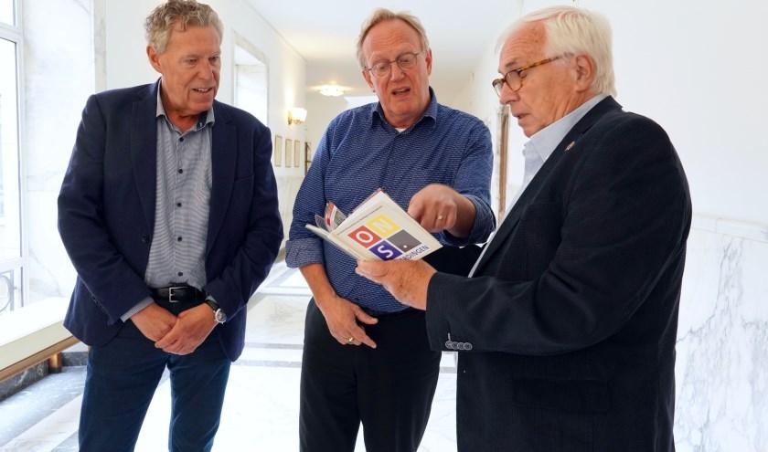 """Raadsleden Ben Vuijk (links) en Gilles Pappes (rechts) reiken Wethouder Bart de Leede hun """"impressie van de stad"""" uit. (Foto: Britt Planken)"""