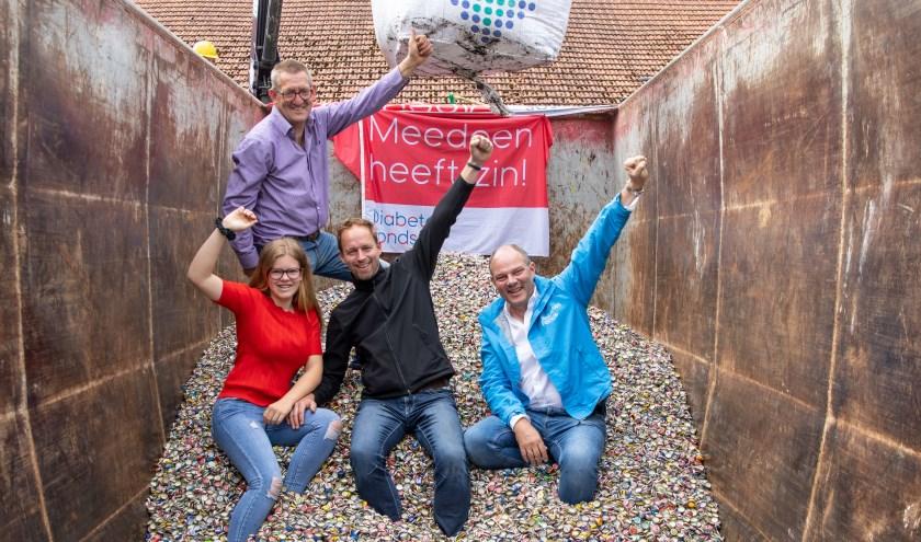In de container, voor v.l.n.r.: Anouk Pinkert, haar vader en initiatiefnemer Arjan Pinkert en Eric Stellwag, manager Fondsenwerving van het Diabetes Fonds. Achter: vrijwilliger Jan Dragt. (foto: Heidie Duteweerdt).