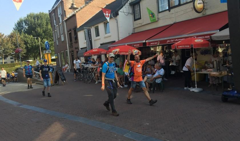 De 50 km-lopers van de Vierdaagse komen op de eerste dag het centrum van Huissen bij de Arnhemse poort binnen,  het terras van 't Huessenaartje biedt de beste plek.