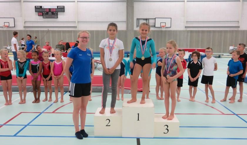 Drie jeugdige winnaars ontvangen een medaille uit handen van Marit Krijgsman (l)