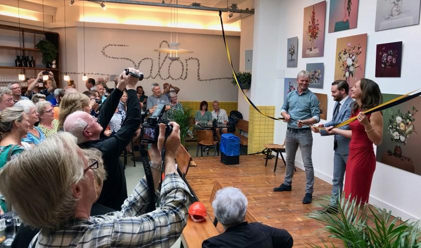 Wethouder Bas Vollebregt knipt met hulp van Marieke en Pascal ter Laak in De Salon het lint door. Foto Rob van Es