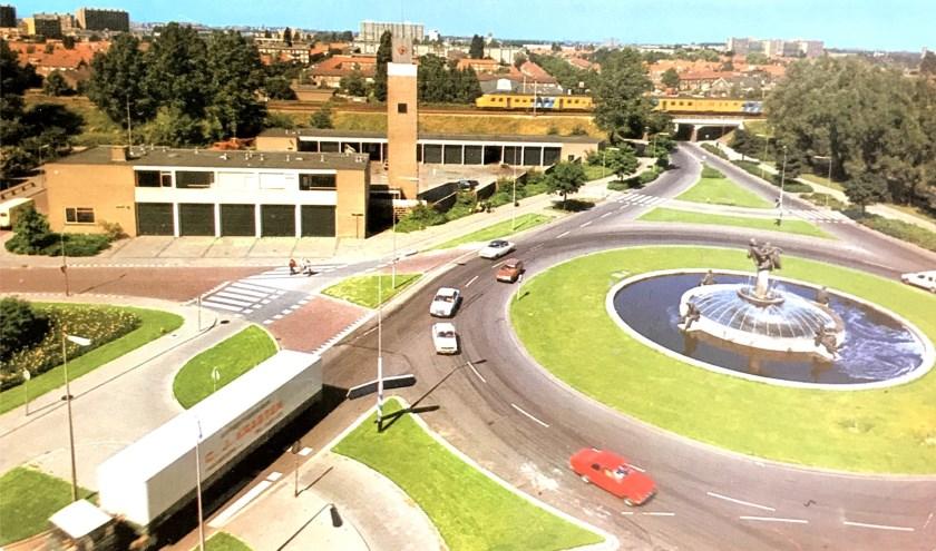 De rotonde aan de Koninginneweg met links de oude brandweerkazerne met de opvallend hoge slangen- en oefentoren. Op de achtergrond de spoorweg. Een ansichtkaart uit de jaren negentig. Collectie HVZ.
