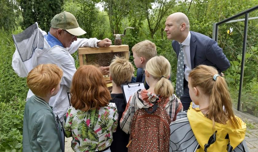 Geïnteresseerd luistert wethouder Armand van de Laar in het Wilhelminapark naar de uitleg van de imker. Erwin Dijkgraaf.