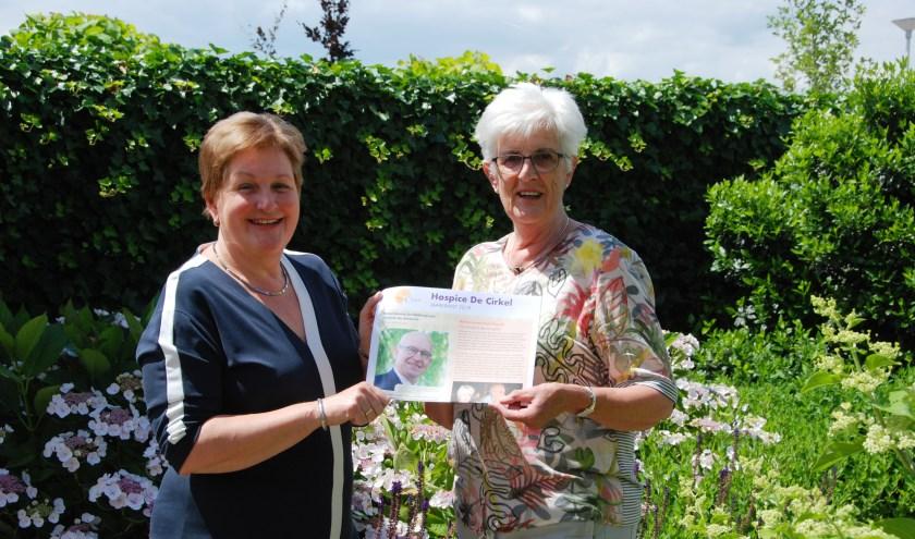 Vrijwilliger Wil Buitenhuis (rechts) krijgt de nieuwe jaarkrant van hospice De Cirkel overhandigd van bestuurslid Heleen Roos. (foto: pr)