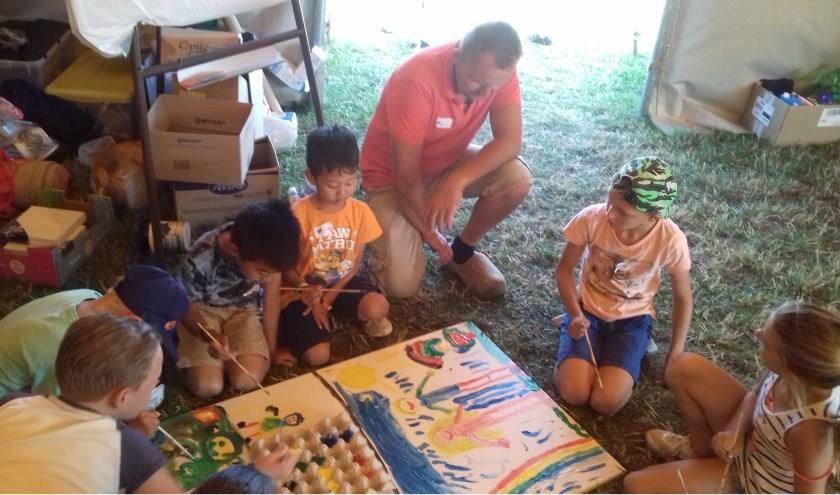 Kinderen maken een kunstwerk van een scheppingsdag