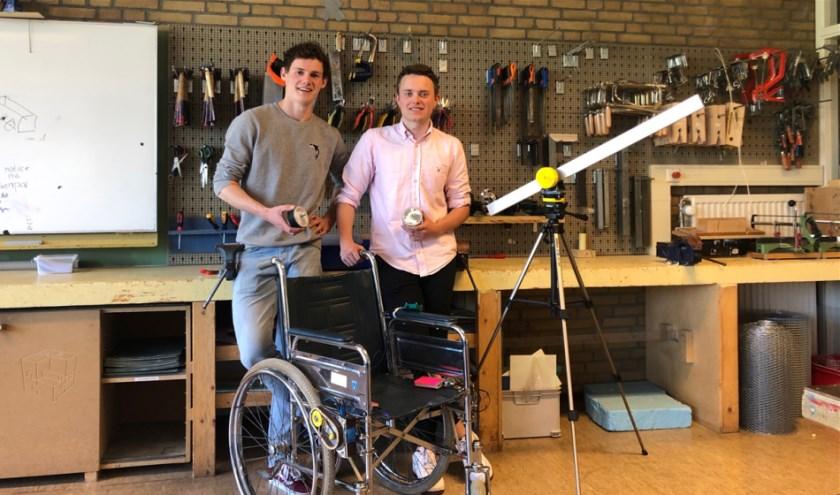 Tom (l) en Cédric in het lokaal van Art & Technology met de robot die onder andere een rolstoel kan bewegen.