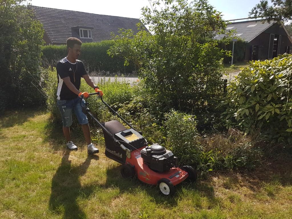 Een van de studenten maait het gras in de voortuin. Foto: Present Winterswijk © DPG Media