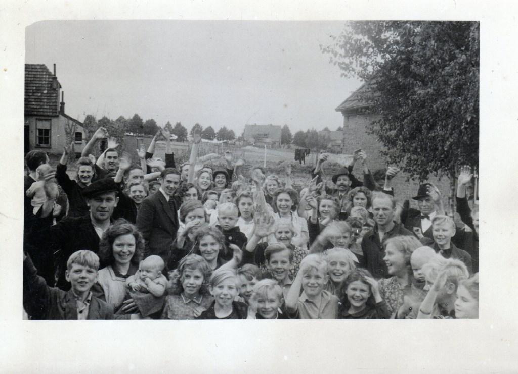 17 februari 1944: Een Amerikaanse soldaat (midden achter met helm) staat tussen zwaaiende Groesbekers op de Leppert/omgeving Stekkenberg met gezicht op de Nieuweweg. (Foto Archief Heemkundekring Groesbeek, collectie G.G. Driessen).  © DPG Media