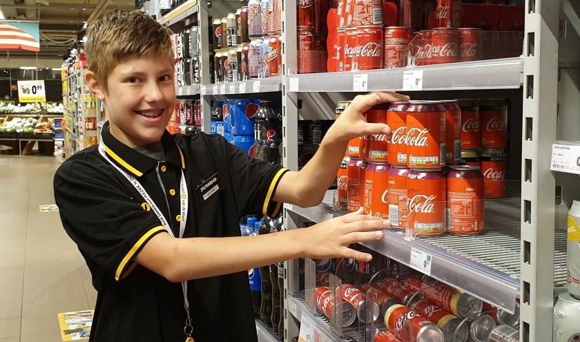Julian geniet ervan om alle producten bij te vullen en weer netjes en strak op een rij te zetten. Foto: Robbert Roos