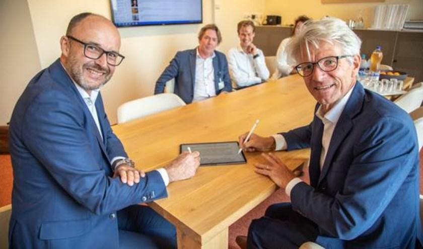 Rob Dillmann (bestuursvoorzitter Isala) en Jan Ramaekers (CEO Sananet) ondertekenen de samenwerking.