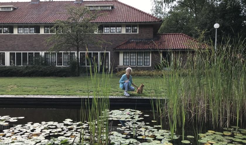 Bianca van Basten met poes Vosje aan één van de twee vijvers tussen de zusterhuizen.