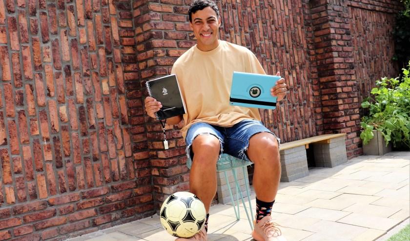 Larry van Ommen behoort tot de moderne trainers die in hun vak gebruikmaken van de laptop. Ook het KNVB-handboek en natuurlijk de bal zijn onmisbaar. Foto: Wout Pluijmert