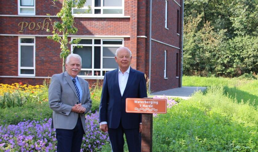 Wethouder Henk Wessel (l.) en ontwilkkelaar Van de Poll (Van de Poll Vastgoed) bij het naambord van de waterberging bij het Poshuys. (Foto: gemeente Elburg)