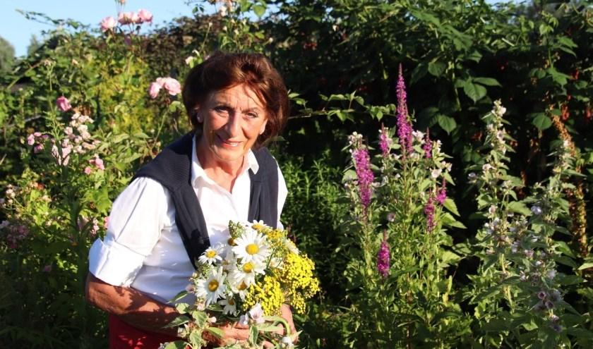 Marianne Knape-Van Santen tussen de bloemen in haar volkstuin in het Kloosterpark. FOTO: Astrid van Walsem