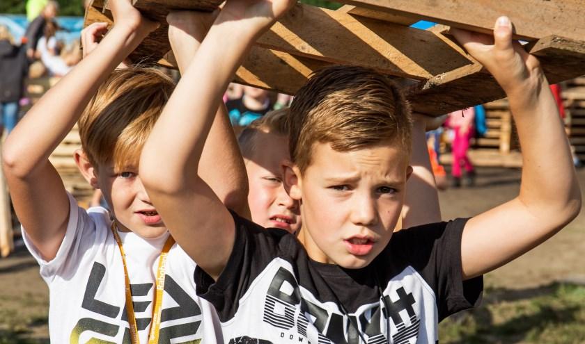 Vele handen maken licht werk, zelfs als het in het Kinderdorp hele zware pallets zijn. (foto: Remko Schotsman)