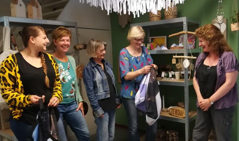 Janny laat details zien van de ZeroWaste-tas. Vanaf links: begeleiders Christa en Ellen; deelnemers Edith, Janny en Betsy. (foto Anja Straathof)