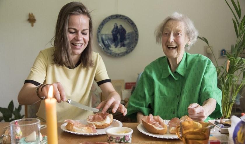 Vrijwilliger Melanie van Stichting Hulpdienst Nijmegen nuttigt samen met mevrouw Beijnes de maaltijd. (Foto Ellen Wissink)
