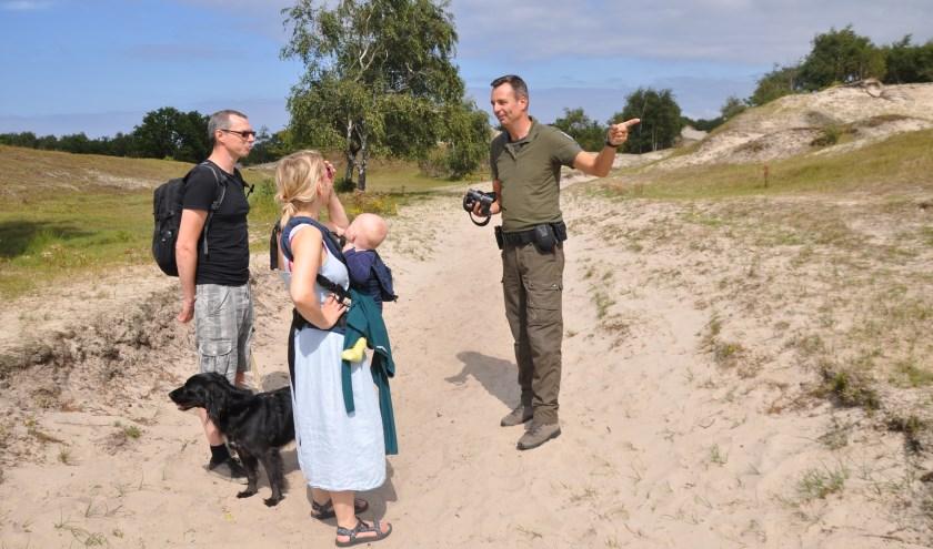 Het is nog twintig minuten lopen naar een plek waar honden los mogen lopen, wijst Sander Penning. FOTO: Anneke Flikweert