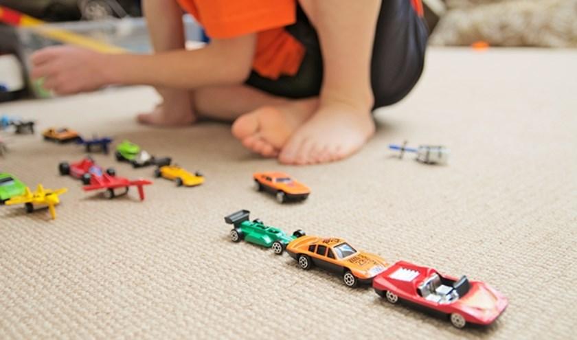 Jongentje speelt met autootjes.