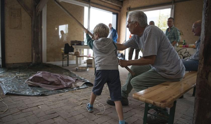 Leo Starink legt een jonge bezoeker uit hoe je met een vlegel moet werken. (foto: Ellen Koelewijn)
