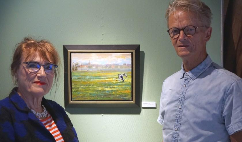 Roeli Rumscheidt en Hans Buenk bij het schilderij 'Koeien in de Hoenwaard'. (foto: Voerman Museum Hattem)