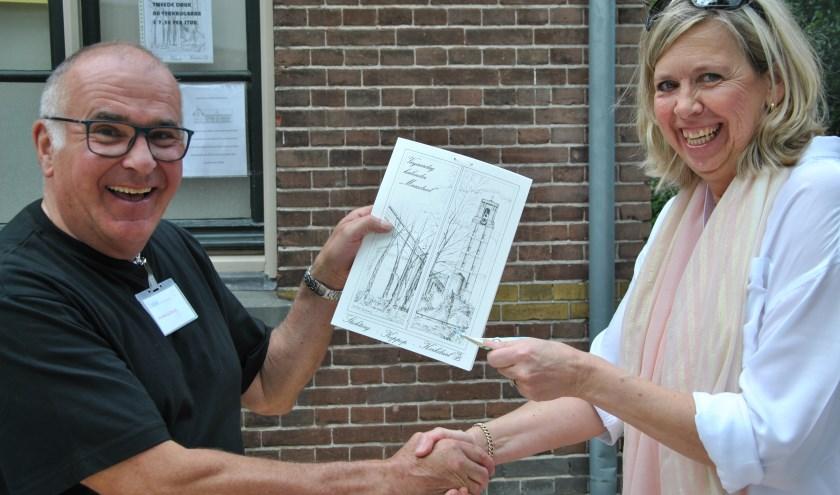 Michel de Bruijn overhandigt Jacqueline Piels (oud-bestuurslid) de verjaardagskalender die opnieuw is uitgegeven.