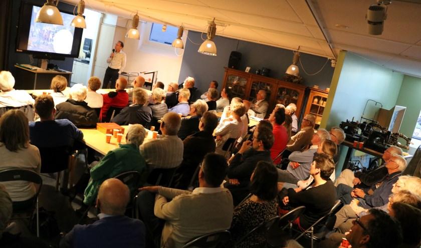 Een afgeladen Koffiehook luistert en kijkt naar de beeldpresentatie van Joop Voortman over de vraag of Rijssen wel of geen echte Hanzestad is geweest.  (Foto: Rijssens Museum)