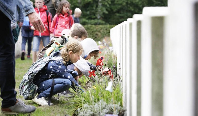 Met ernstige gezichten worden de zelfgemaakte bloemen op het graf van Walter Batchelor gelegd. (Foto: Jurgen van Hoof).
