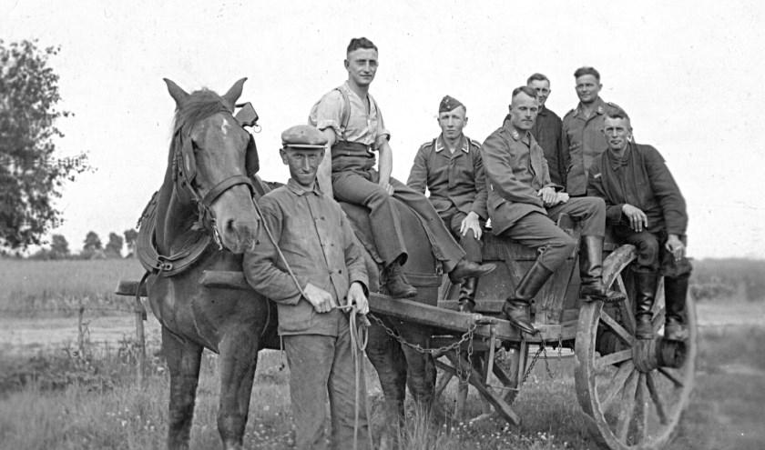 Frans van Loon (links) met op zijn kar Duitsers die wel eens hielpen op de boerderij.