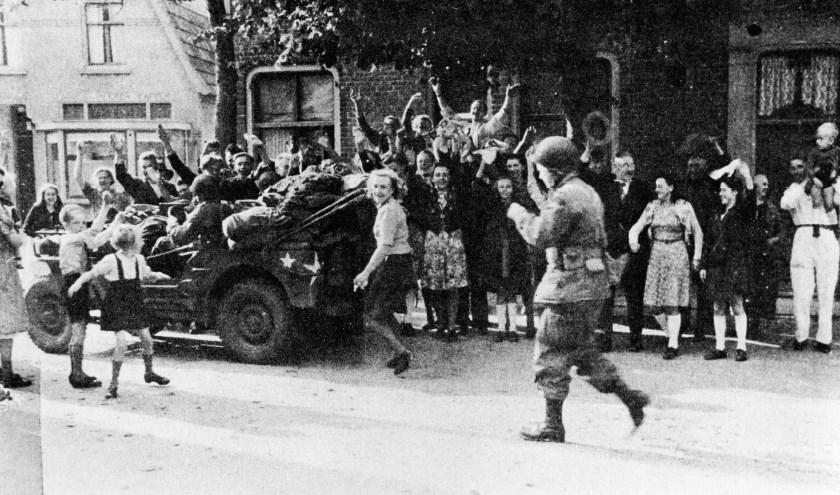 17 februari 1944: In de Groesbeekse Dorpsstraat bij de afslag Mooksestraat (ter hoogte van het huidige Dorpsplein) juichen buurtbewoners de bevrijders toe. (Foto Archief Heemkundekring Groesbeek, collectie G.G. Driessen).