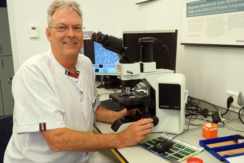 Paul Wubbels bezig met bloedonderzoek achter de microscoop. (foto: Tom Oosthout)